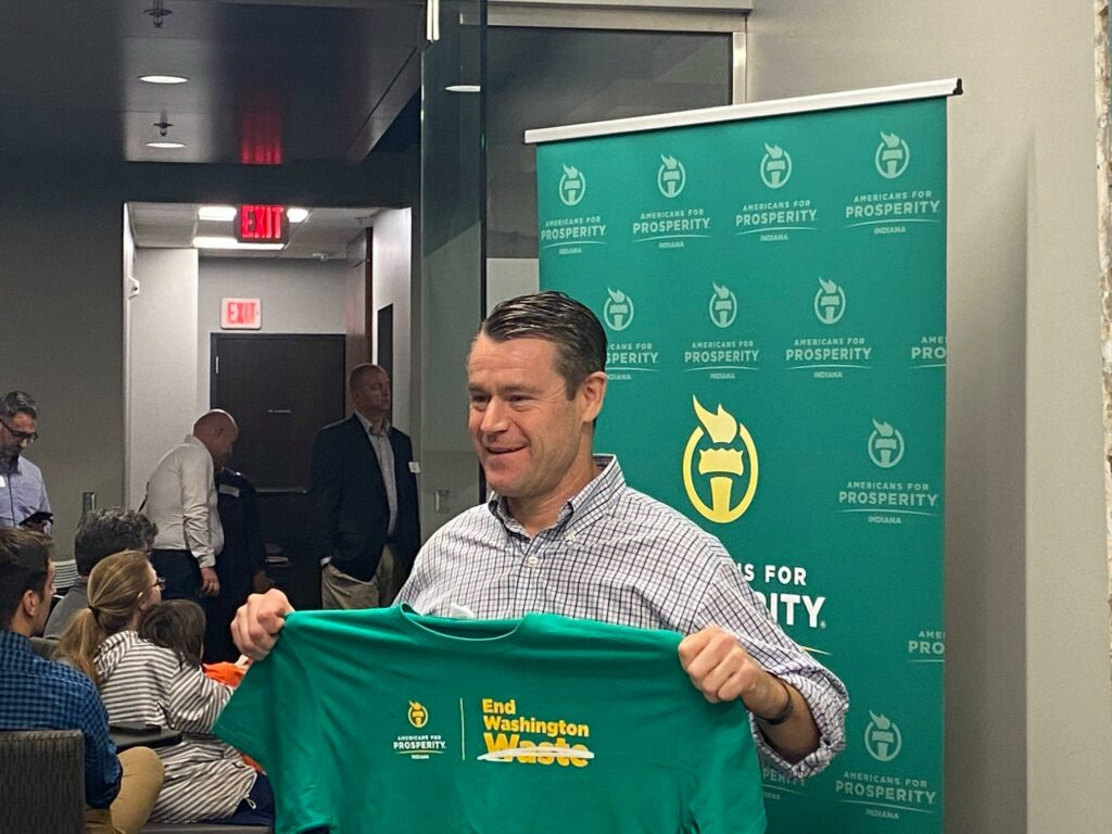 Senator Todd Young holds up one of Americans for Prosperity's End Washington Waste t-shirts at an event with activists and AFP President Tim Phillips
